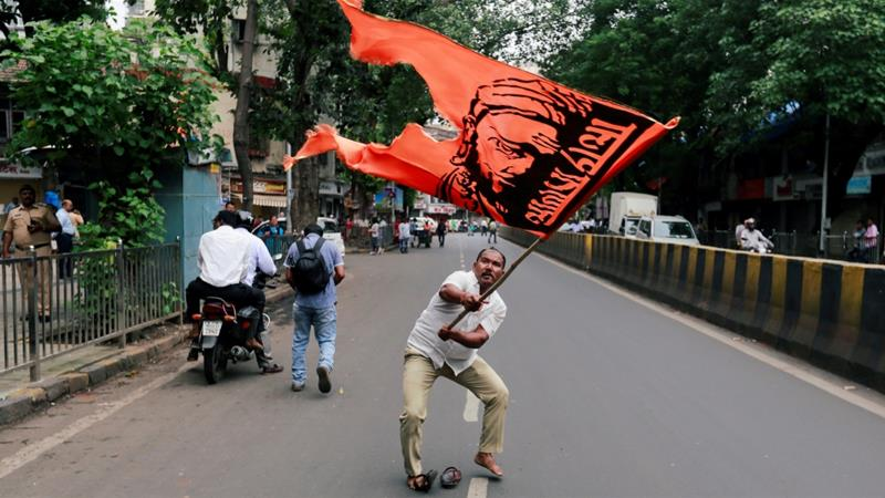 A man waves a flag as he blocks a road during a protest organised by Maharashtra state's Maratha community to press their demands [Danish Siddiqui/Reuters]