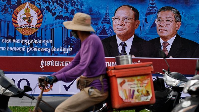A cyclist rides past an image of Cambodia's Prime Minister and leader of the ruling Cambodian People's Party, Hun Sen, in Phnom Penh [Manan Vatsyayana/AFP]