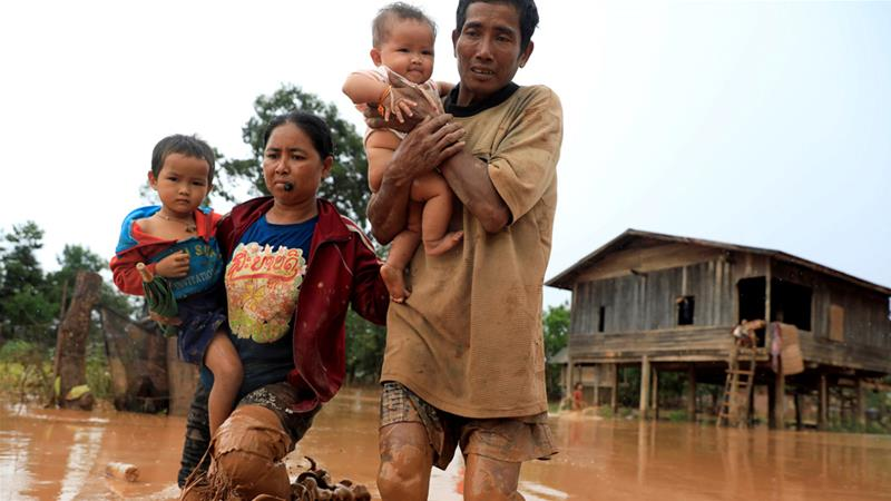 Parents carry their children as they flee the flood after the Xepian-Xe Nam Noy dam burst [Soe Zeya Tun/Reuters]