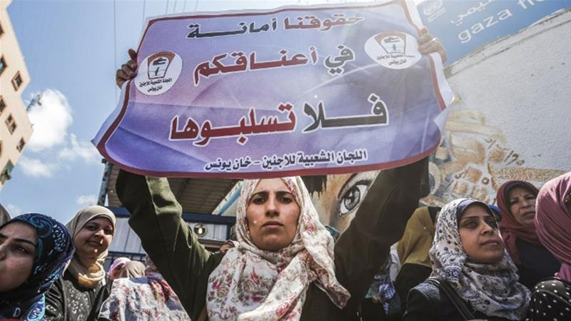 A woman holds a sign reading 'We trust you with our rights, please do not rob them' during a demonstration by UNRWA employees [Mahmud Hams/AFP]