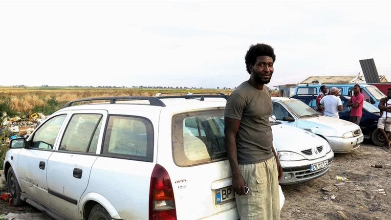 Malian Ibrahim Assanoko leans on a car labourers use to reach work. He made better money elsewhere in Europe, but was forced back to Italy under the Dublin Regulation [Elisa Oddone/Al Jazeera]