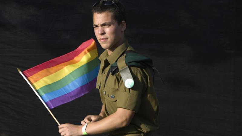 An Israeli soldier holds a flag as he takes part in the gay pride parade in Jerusalem [File photo: Reuters/Baz Ratner]