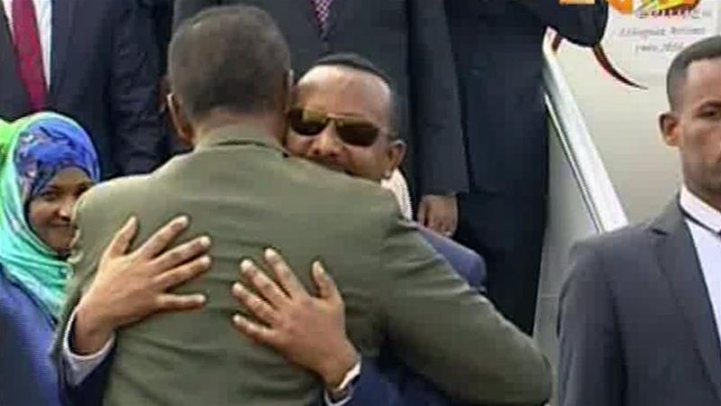In this grab taken from video provided by ERITV, Ethiopia's Abiy Ahmed is welcomed by Eritrea's Isaias Afwerki as he disembarks the plane in Asmara, Eritrea on July 8, 2018 [ERITV via AP]