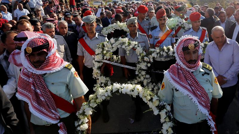 An honour guard walks with relatives of Sergeant Hisham Aqarbeh who was killed during an attack [Muhammad Hamed/Reuters]