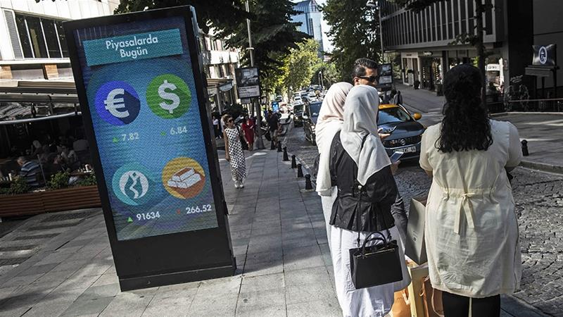 Women stand next to a billboard giving currencies rates in a street in Istanbul on August 13 [Yasin AKGUL/AFP]