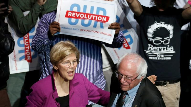 Senator Elizabeth Warren puts her arm around Senator Bernie Sanders after introducing him at a Our Revolution rally in Boston, Massachusetts, US March 31, 2017 [Mary Schwalm/Reuters]