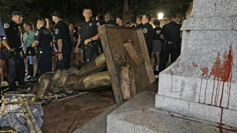Police stand guard after the Confederate statue known as Silent Sam was toppled by protesters [Gerry Broome/AP Photo]