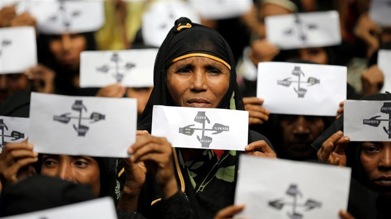 Rohingya women hold placards as they protest at Kutupalong refugee camp [Mohammad Ponir Hossain/Reuters]