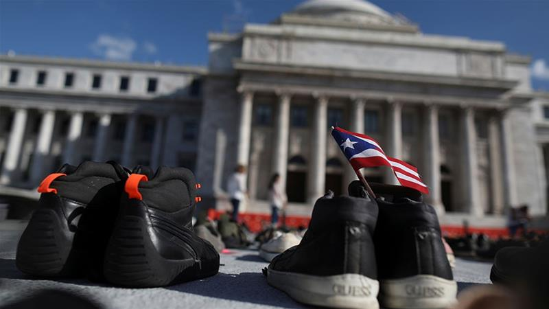 A Puerto Rican flag is seen on a pair of shoes as hundreds of pairs of shoes displayed at the US Capitol to pay tribute to Hurricane Maria's victims [File: Alvin Baez/Reuters]