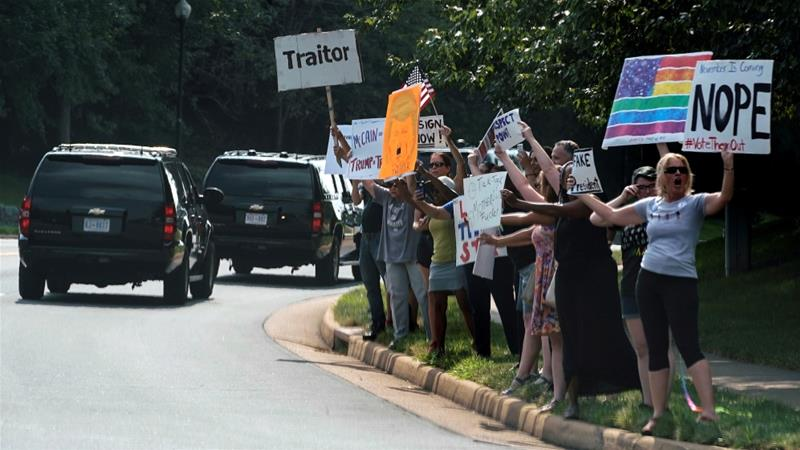 Protesters wave signs at the motorcade carrying US President Donald Trump as he departs from the Trump National Golf Club in Sterling, Virginia, US, August 26, 2018 [Joshua Roberts/Reuters]