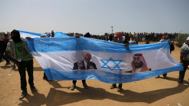 Palestinian demonstrators hold a representation of an Israeli flag with pictures of Donald Trump and Mohammed bin Salman during a protest in the Gaza Strip, on April 13 2018 [Abu Mustafa/Reuters]