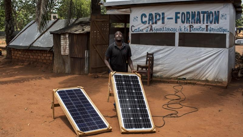 Salet, who is also displaced, repositions solar panels outside the computer lab. He's rigged up a car battery to the panels so students have a relatively steady power supply [Will Baxter/Al Jazeera]