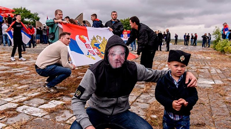 A young man wearing a mask depicting Serbian war criminal Ratko Mladic takes part in a ceremony on the outskirts of Pristina, marking the landmark 'Battle of Kosovo' [Armend Nimani/AFP/Getty Images]
