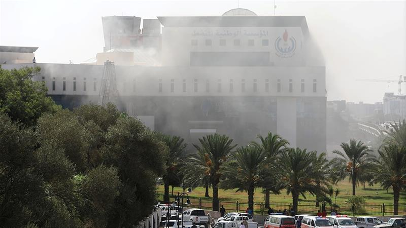 Smoke shrouded the headquarters of the National Oil Corporation (NOC) in Tripoli [Hani Amara/Reuters]