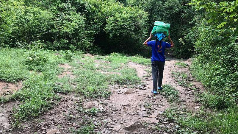Cecilia Lopez, 18, carries a bag of fertilizer to her family's plot of corn in the village of El Milagro [Heather Gies/Al Jazeera]