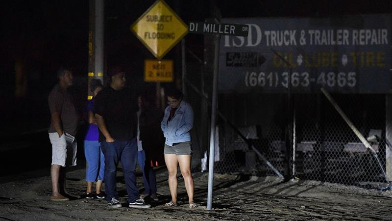 Relatives of victims stand outside the scene of the shooting that resulted in the deaths of six people in Bakersfield, California  [Mark Ralston/AFP]