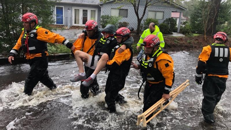 Rescue workers carry a man to safety in River Bend, New York [NYC Emergency Management/Reuters]