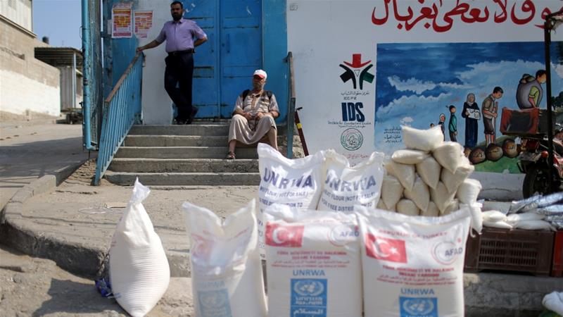 A Palestinian man sits outside an aid distribution centre run by UNRWA in Khan Younis in the southern Gaza Strip [Ibraheem Abu Mustafa/Reuters]