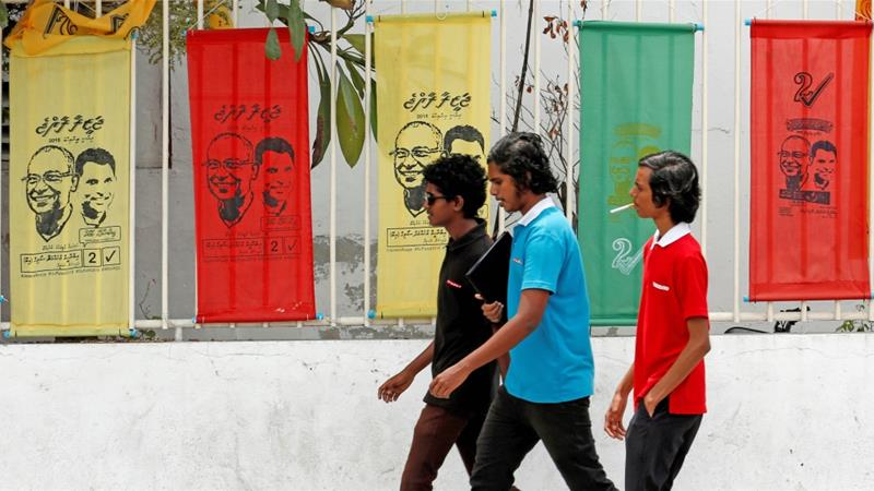 Youths walk past the posters of Ibrahim Mohamed Solih, Maldivian presidential candidate backed by the opposition coalition, in Male, Maldives on September 19, 2018 [Reuters/Ashwa Faheem]
