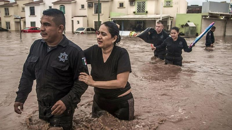 Police officers help a woman cross a flooded street in Sinaloa State, Mexico [Rashide Frias/ AFP]