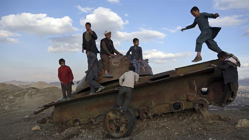 Afghan children play on the remains of a Soviet tank on a hilltop on the outskirts of Kabul last March [Rahmat Gul/AP]
