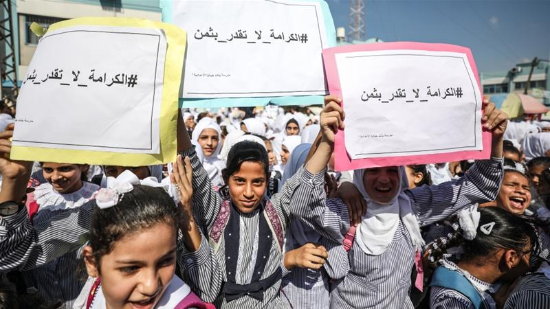 Palestinian children hold banners that say 'dignity is priceless' during a protest against UNWRA job cuts to dismiss personnel in Gaza City [File: Anadolu Agency]