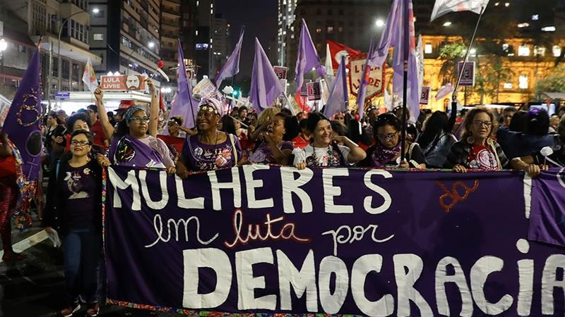 Women hold a banner reading 'Women struggle for democracy' during a campaign rally of presidential candidate Fernando Haddad [Andre Penner/AP Photo]
