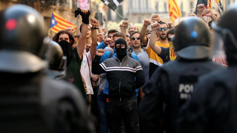 Catalan separatists stand face police officers as another group marches in support of the Spanish police units who tried to prevent the independence referendum [Jon Nazca/Reuters]
