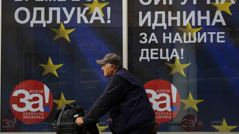 A man passes next to posters reading 'yes' for the referendum in Macedonia on changing the country's name [Marko Djurica/Reuters]