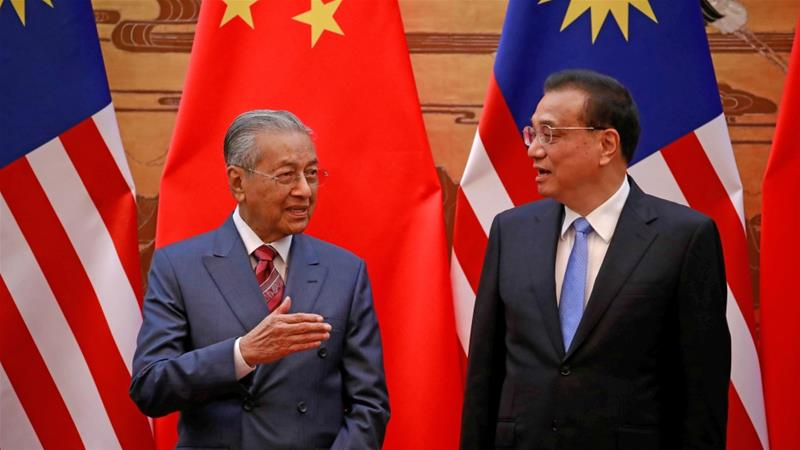 Malaysia's Prime Minister Mahathir Mohamad and China's Premier Li Keqiang chat during a signing ceremony at the Great Hall of the People in Beijing on August, 20, 2018 [How Hwee Young/Reuters]