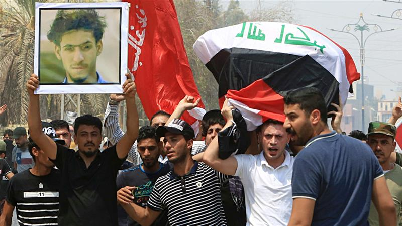 Mourners carry the Iraqi flag-draped coffin of Yasser Makki who was killed in a demonstration on Monday [Nabil al-Jurani/AP]