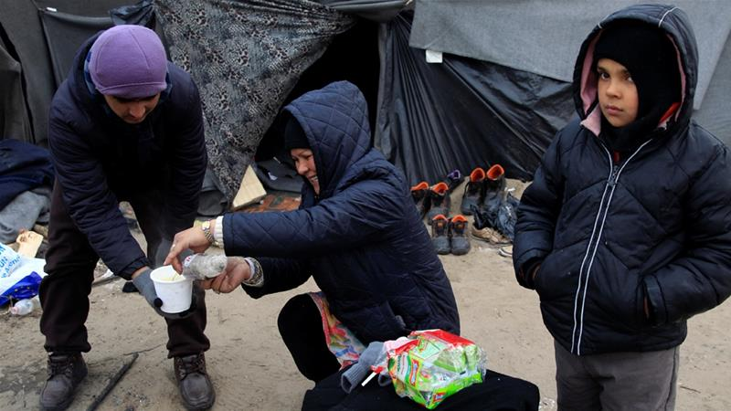 Migrants prepare food at a transit zone on the Serbian-Hungarian border in early 2017 [File: Reuters]