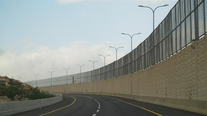 West Bank: Israelis, Palestinians separated by wall on road
