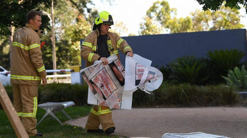 A firefighter carries a hazardous material bag into a consulate in Melbourne on Wednesday after suspicious packages were sent to foreign missions around the city