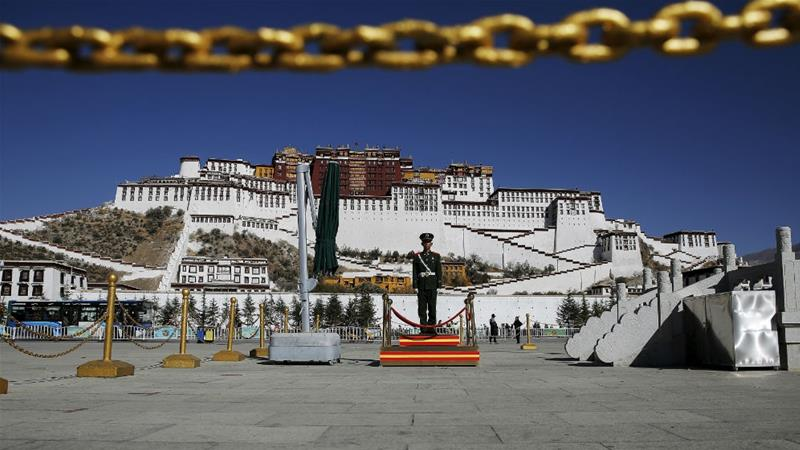 A paramilitary officer stands guard in front of the Potala Palace in Lhasa, the capital of the Tibet Autonomous Region; the palace was once the seat of the Tibetan government and the traditional residence of Dalai Lama [File: Damir Sagol/Reuters]