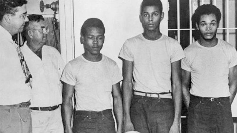 Lake County Sheriff Willis McCall (far left) and an unknown man standing next to Walter Irvin, Samuel Shepherd and Charles Greenlee [File: State Library and Archives of Florida/AP]
