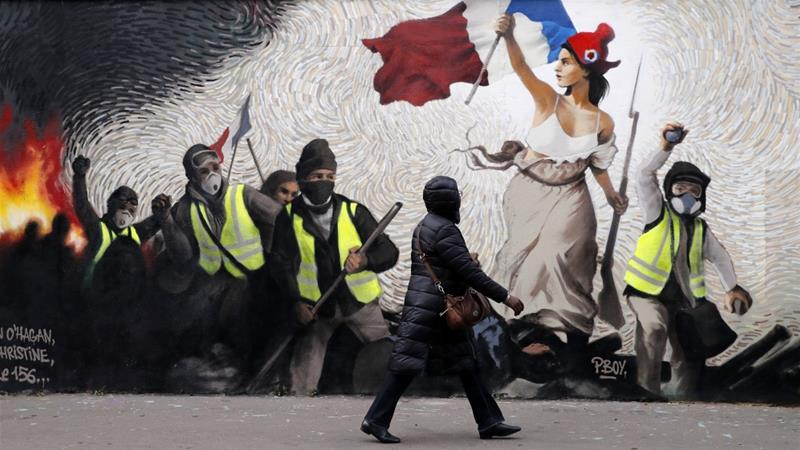 A woman passes by a mural by street artist PBOY depicting yellow vest protesters [Christophe Ena/AP]
