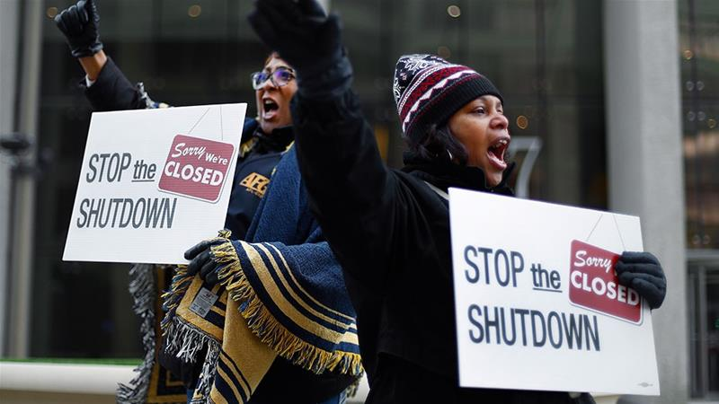 Cheryl Monroe right a Food and Drug Administration employee and Bertrice Sanders a Social Security Administration employee rally to call for an end to the partial government shutdown in Detroit