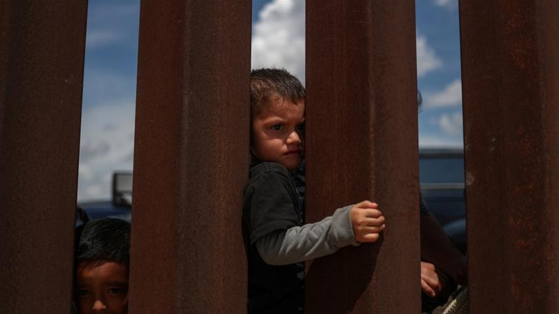 Undocumented immigrant children look back towards Mexico through the border wall as they await apprehension after crossing into the US from Mexico in August 2018 [File: Adrees Latif/Reuters]