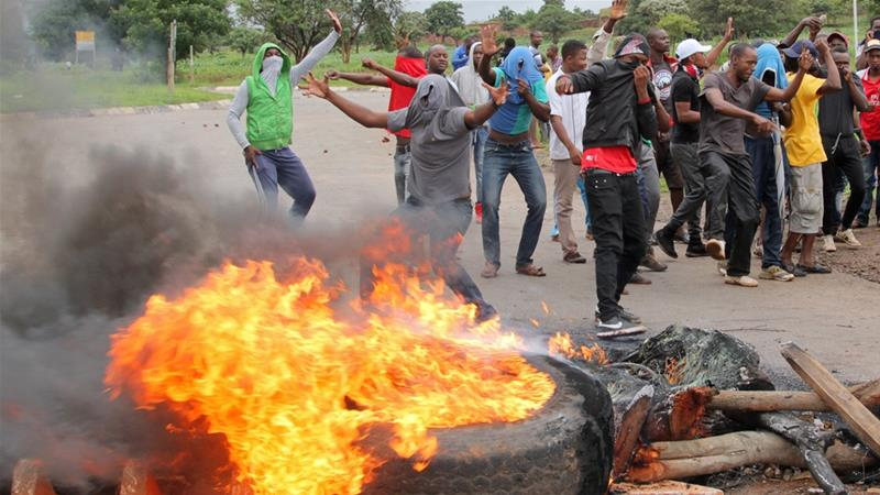 Protesters stand behind a burning barricade during protests on a road leading to Harare on January 15 [Philimon Bulawayo/Reuters]