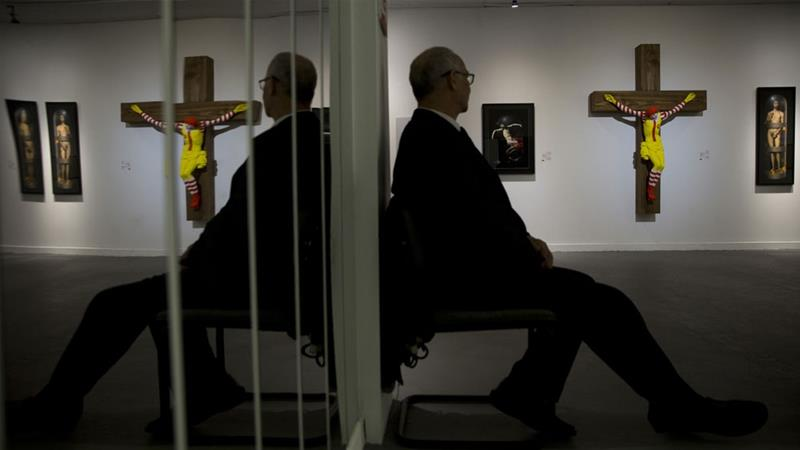 An artwork called 'McJesus,' which depicts a crucified Ronald McDonald, is seen on display as part of the Haifa museum''s 'Sacred Goods' exhibit, in Haifa, Israel [AP/Oded Balilty]