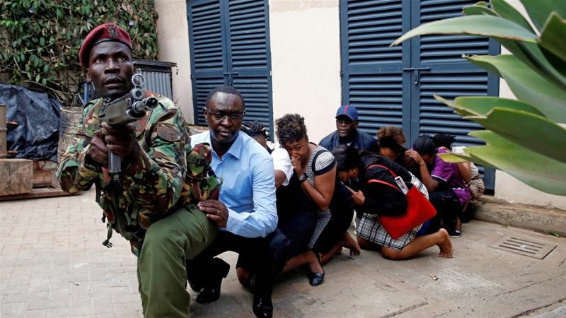 People are evacuated by a member of security forces at the scene where explosions and gunshots were heard at the Dusit Hotel compound in Nairobi, Kenya on January 15, 2019 [Reuters/Baz Ratner]