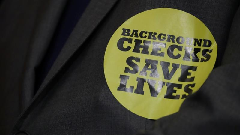 A member of Congress wears a 'Background Checks Save Lives' sticker [File: Jonathan Ernst/Reuters]