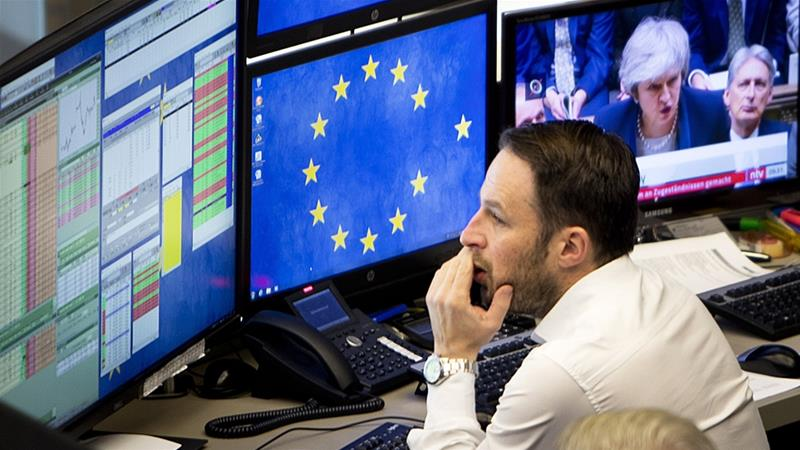 A computer screen shows news about Brexit as a broker watches his screens at the stock market in Frankfurt, Germany [File: Michael Probst/The Associated Press]
