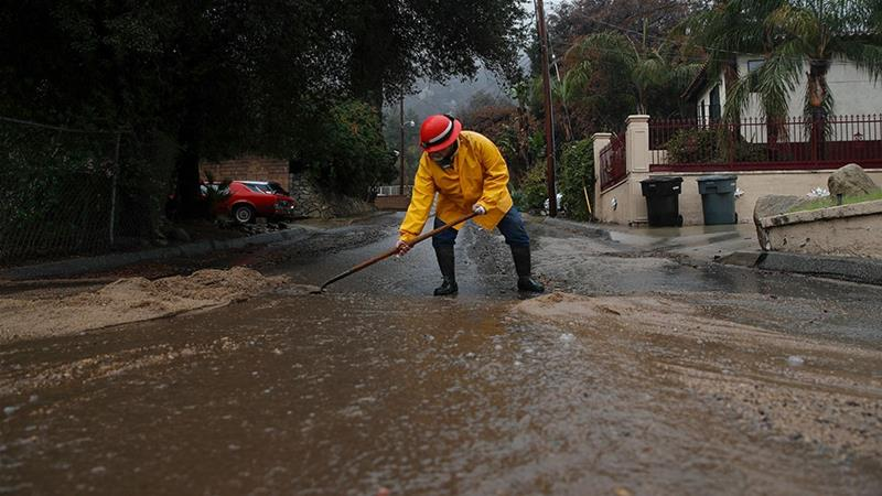 Albert McGowan, 63, uses a shovel to redirect water in Lake Elsinore, California [Jae C Hong/AP Photo]