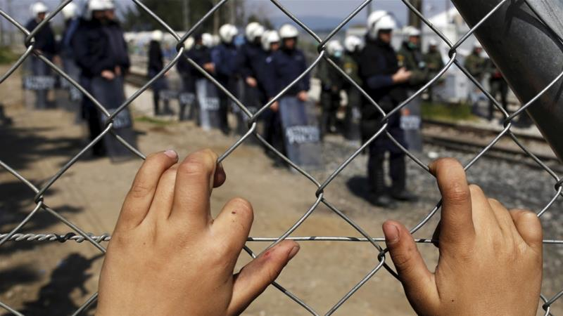 File: A child refugee places his hands on a fence as police officers stand guard at a makeshift refugee camp  at the Greek-Macedonian border [File:Marko Djurica/Reuters]