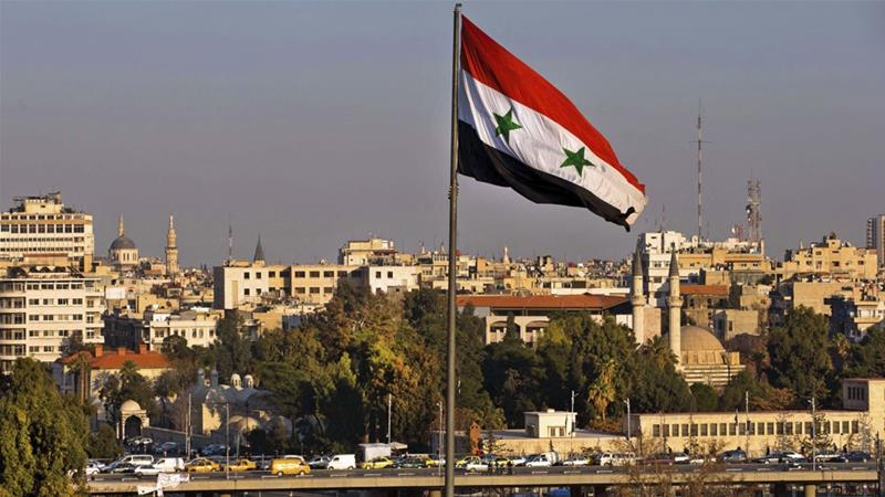 A Syrian national flag waves as vehicles move on a bridge during rush hour, in Damascus [File: Hassan Ammar/AP]