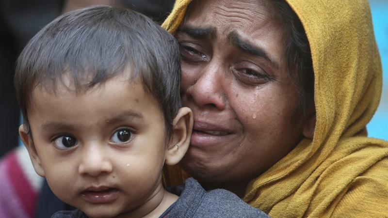 A Rohingya woman cries as she holds her daughter after they were detained while crossing the India-Bangladesh border [Jayanta Dey/Reuters]