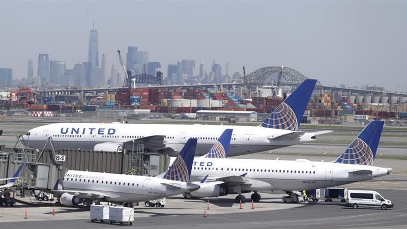 The New York City skyline is seen at a distance as United Airlines jets sit at gates at Newark Liberty International Airport [File: Julio Cortez/AP Photo]
