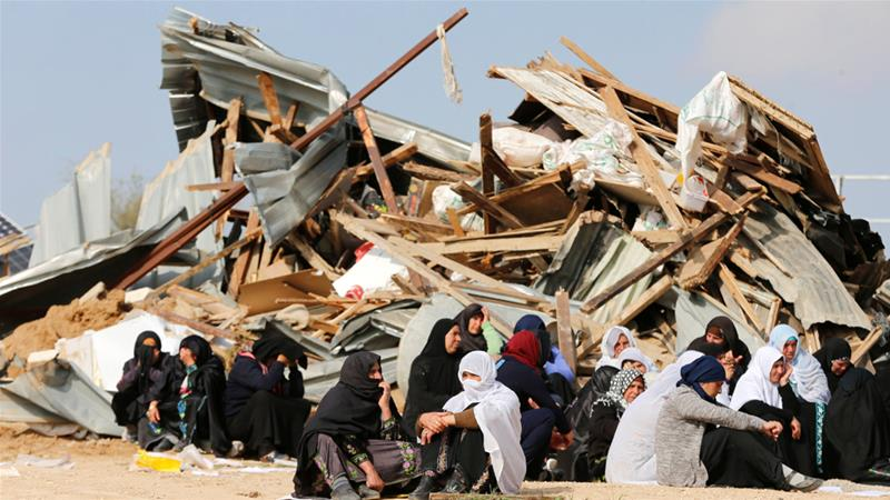 Bedouin women sit next to the ruins of their dwellings demolished by Israeli bulldozers in Umm Al-Hiran [File: Ammar Awad/Reuters]